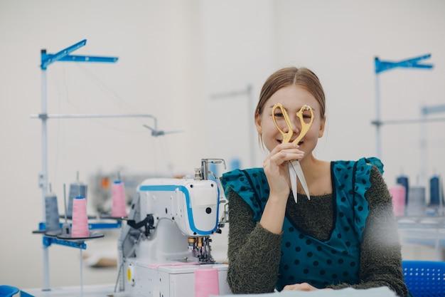 La giovane bella cucitrice cuce sulla macchina per cucire in fabbrica