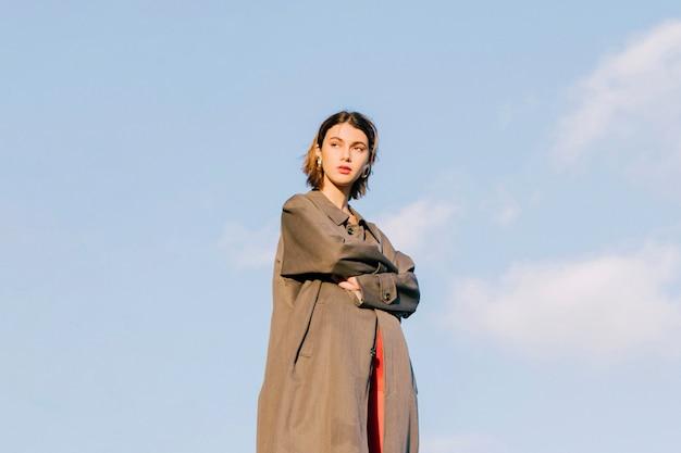 La giovane bella donna alla moda con le sue armi ha attraversato la condizione contro il cielo blu