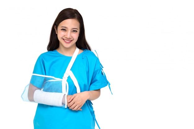 La giovane bella donna asiatica che indossa le attrezzature pazienti e ha messo sopra una stecca molle a causa di un braccio rotto isolato, concetto personale di incidente
