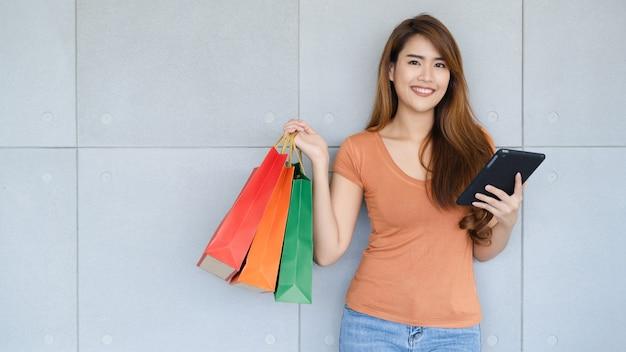 La giovane bella donna asiatica che sta con lo smiley sta usando la compressa o lo smartphone