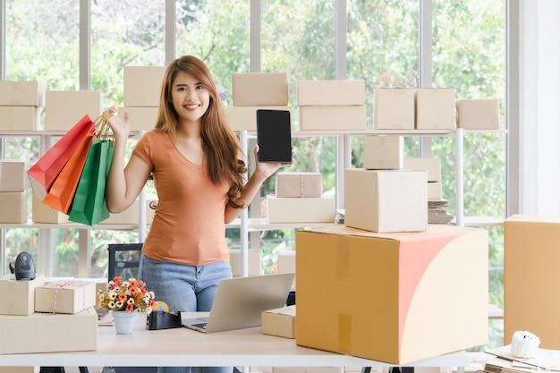 La giovane bella donna asiatica felice di affari sta stando e tenendo una compressa