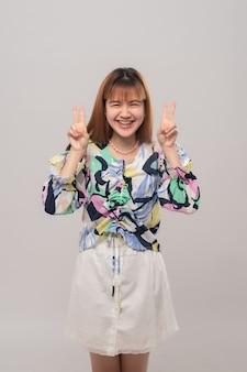 La giovane bella donna asiatica in parentesi graffe che porta la camicia variopinta che sorride mostrando le dita che fanno il segno di vittoria. felice concetto femminile.