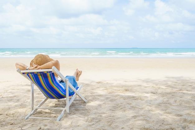 La giovane bella donna asiatica si rilassa al sole sulle sedie sulla spiaggia vicino al mare.