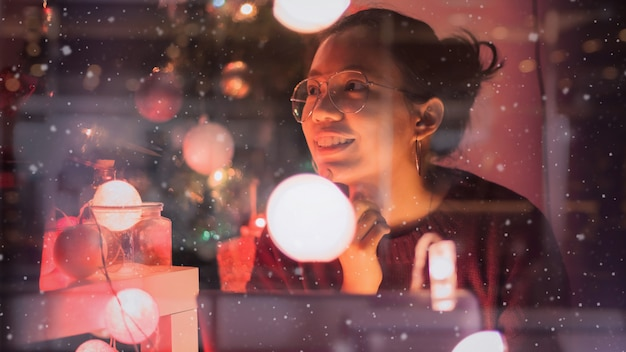 La giovane bella donna asiatica si sente bene con le celebrazioni del nuovo anno con il contenitore di regalo nella casa decora con l'albero di natale concetto di buone feste riflessione della finestra di vetro ed effetto della neve.