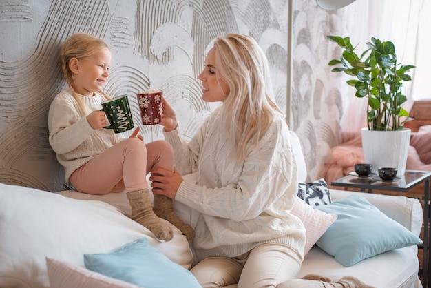 La giovane bella donna bionda abbraccia la sua piccola figlia sul divano con tazze di bevanda calda.
