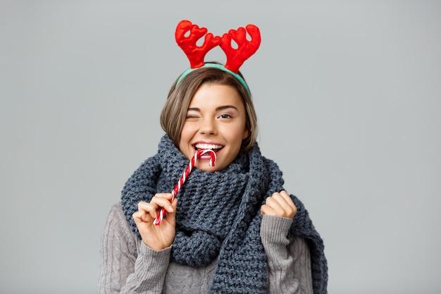 La giovane bella donna bionda in grandi corna tricottate della renna di natale e della sciarpa che sorride mangiando il lollypop a strisce su gray.