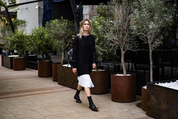 La giovane bella donna cammina intorno alla città