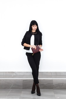La giovane bella donna castana seria con un taccuino si è vestita in un vestito nero che sta contro la parete bianca in ufficio.