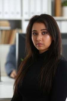 La giovane bella donna castana si siede alla tavola in ufficio in gabinetto del suo capo