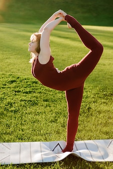 La giovane bella donna che fa l'yoga si esercita in parco
