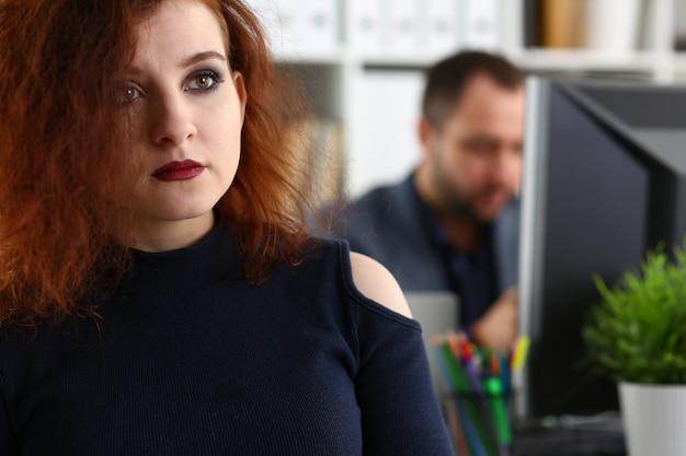 La giovane bella donna dai capelli rossi si siede al tavolo in ufficio nel gabinetto del suo capo
