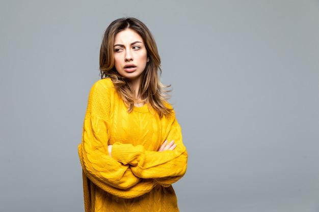 La giovane bella donna in maglione casuale giallo che sta con le armi ha attraversato isolato sulla parete grigia