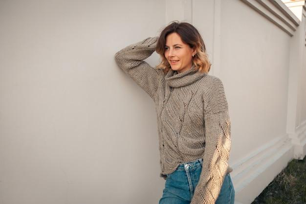 La giovane bella donna in marrone tricotta il maglione nel parco di autunno. concetto di autunno a piedi.