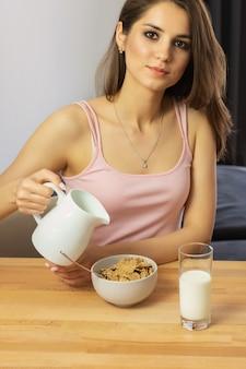 La giovane bella donna mangia i cereali da prima colazione con le bacche e il latte.