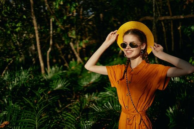 La giovane bella donna nella giungla dei tropici con il cappello cammina nel parco, naturalista