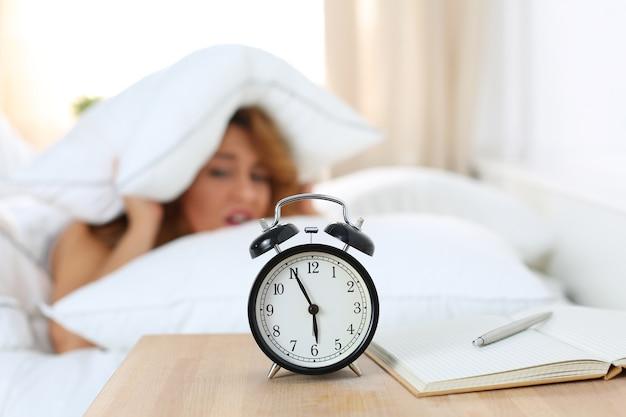 La giovane bella donna odia svegliarsi presto la mattina. ragazza sonnolenta guardando la sveglia e cercando di nascondersi sotto il cuscino