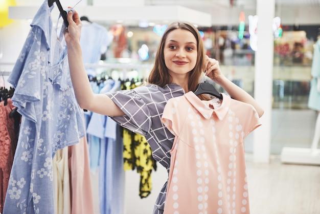 La giovane bella donna sorridente fa la scelta quando fa acquisti in un negozio
