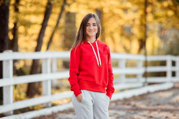 La giovane bella donna sportiva in un maglione rosso si diverte nel parco d'autunno