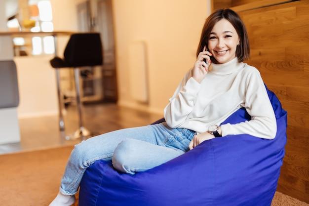 La giovane bella donna sta sedendosi nella sedia di borsa viola luminosa facendo uso del suo sms del telefono