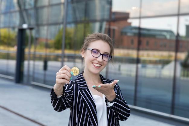 La giovane bella donna tiene bitcoin in una mano. è una donna d'affari e ha investito i suoi soldi in criptovaluta, progettando di fare buoni soldi su di essa.