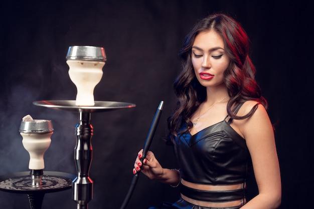 La giovane bella femmina in vestito nero che fuma ed espira il narghilé