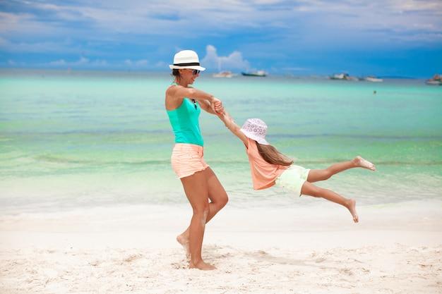 La giovane bella madre e la sua adorabile piccola figlia si divertono in spiaggia tropicale