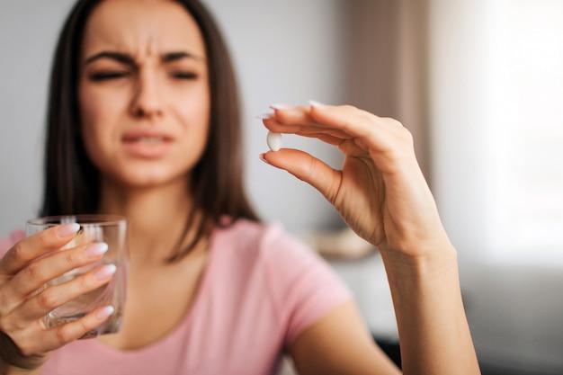 La giovane bella modella tiene la pillola bianca tra le dita e la guarda. lei ha un bicchiere d'acqua. il modello deve bere acqua con la pillola. lei si restringe. la giovane donna soffre.