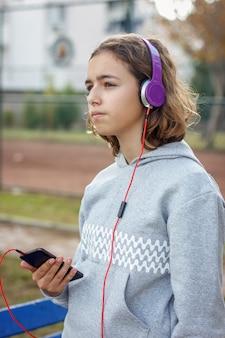 La giovane bella ragazza alla moda dell'adolescente ascolta musica sulle cuffie da uno smartphone