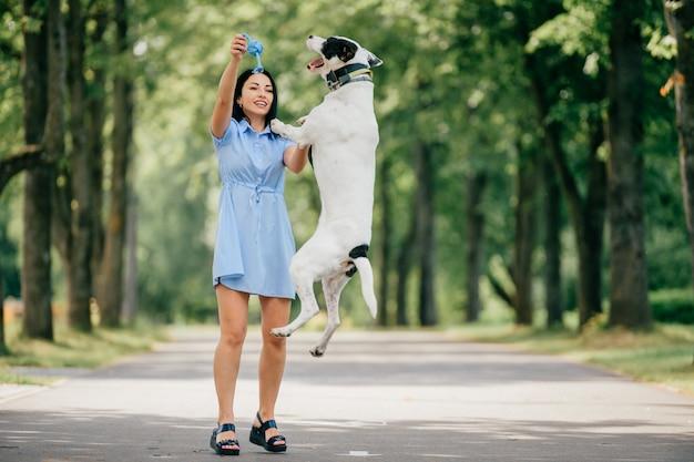 La giovane bella ragazza allegra castana in vestito blu si diverte e gioca con il suo cane bianco maschio all'aperto alla natura. la donna di bell'aspetto ama gli animali gentili