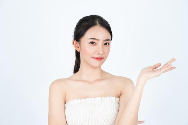 La giovane bella ragazza asiatica in maglietta bianca, ha la pelle sana e luminosa, presentando il prodotto.