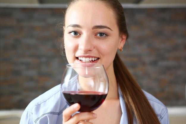 La giovane bella ragazza attraente beve il vino
