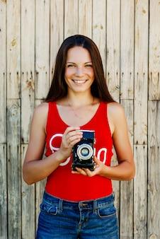 La giovane bella ragazza castana in jeans rossi della camicia e dei jeans mette in posa con una macchina fotografica sui precedenti di legno rustici.
