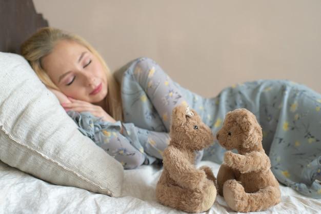 La giovane bella ragazza che dorme sul letto con il bambino gioca come il bambino.