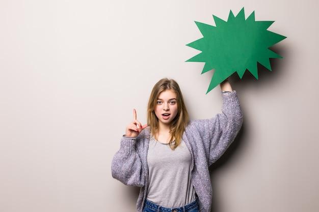 La giovane bella ragazza che tiene una bolla verde ha idea, isolata