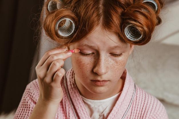 La giovane bella ragazza fa il trucco sul letto nella camera da letto. dai capelli rossi e calafataggio con i bigodini in testa in un accappatoio.