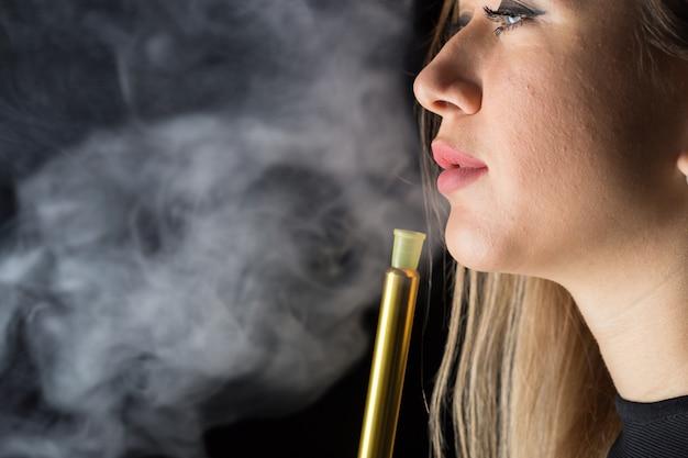 La giovane, bella ragazza fuma un narghilé