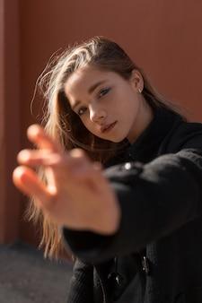 La giovane bella ragazza in cappotto nero il giorno soleggiato allunga la sua mano in avanti. distribuire attenzione.