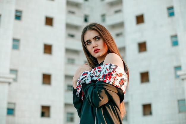 La giovane bella ragazza in una giacca nera con una sciarpa posa vicino ad un'alta casa bianca.
