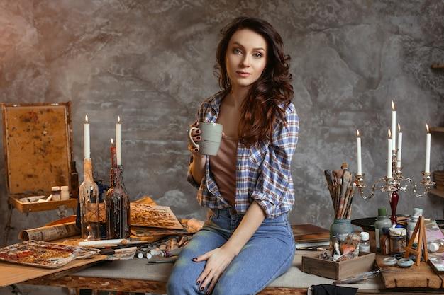 La giovane bella ragazza pittore con una tazza di caffè sedersi sul tavolo in officina.