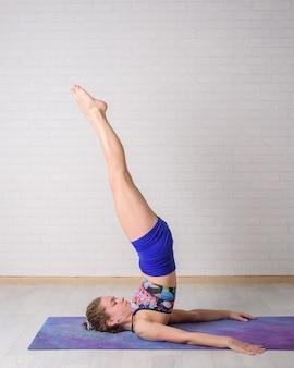 La giovane bella ragazza pratica l'yoga a casa.