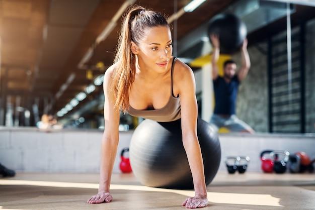 La giovane bella ragazza sportiva che fa alcuni spinge aumenta mentre si trova su una palla dei pilates.