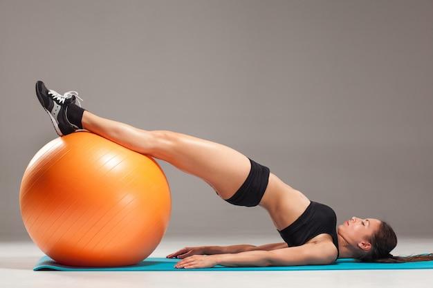 La giovane, bella ragazza sportiva che fa esercizi su fitball