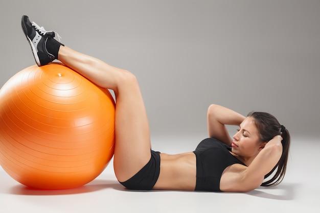 La giovane, bella ragazza sportiva che fa esercizi su un fitball