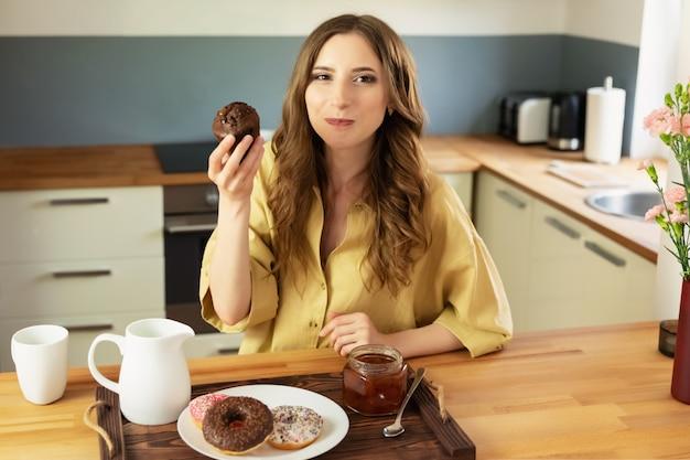 La giovane bella ragazza sta facendo colazione a casa in cucina. beve il caffè del mattino e mangia un muffin al cioccolato.