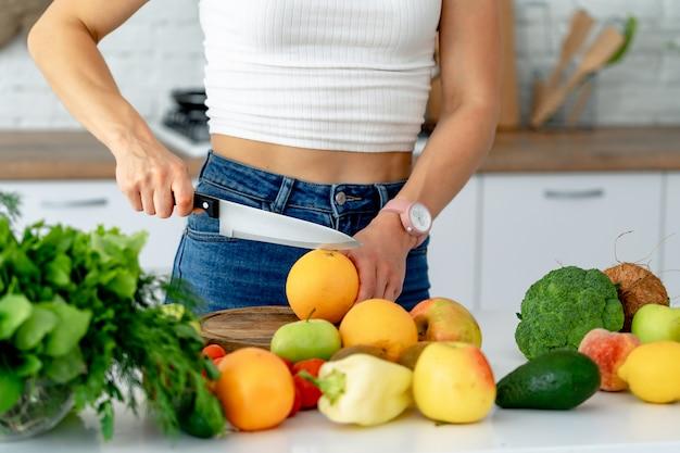 La giovane bella ragazza taglia l'arancia fresca per preparare il succo fresco nella cucina