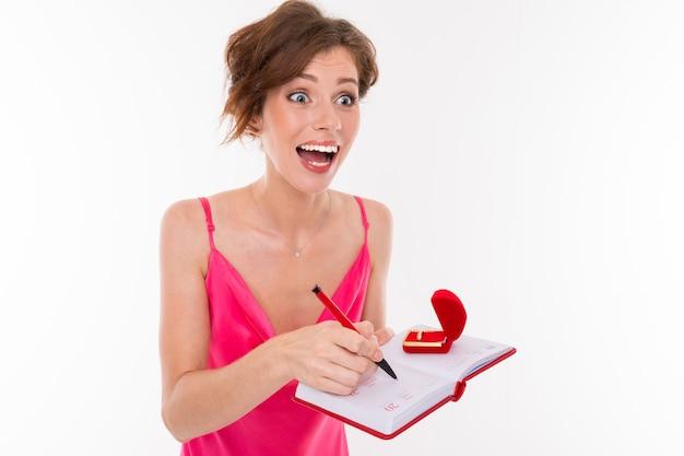 La giovane bella ragazza tiene una scatola per un anello di fidanzamento e le nozze di pianificazione isolate su bianco