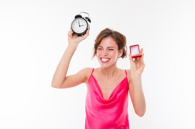 La giovane bella ragazza tiene una scatola per un anello di fidanzamento e lo mostra sulla sua mano isolata su bianco
