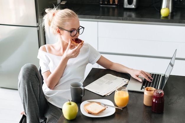 La giovane bella signora fa colazione e utilizza il computer portatile nella cucina