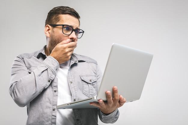 La giovane brunetta emotiva stupita con setola con una smorfia triste guarda lo schermo del dispositivo