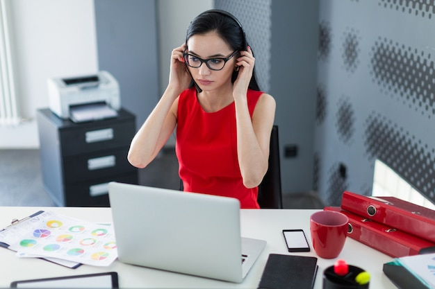 La giovane businesslady attraente in vestito e vetri rossi si siede alla tavola e lavora con il computer portatile